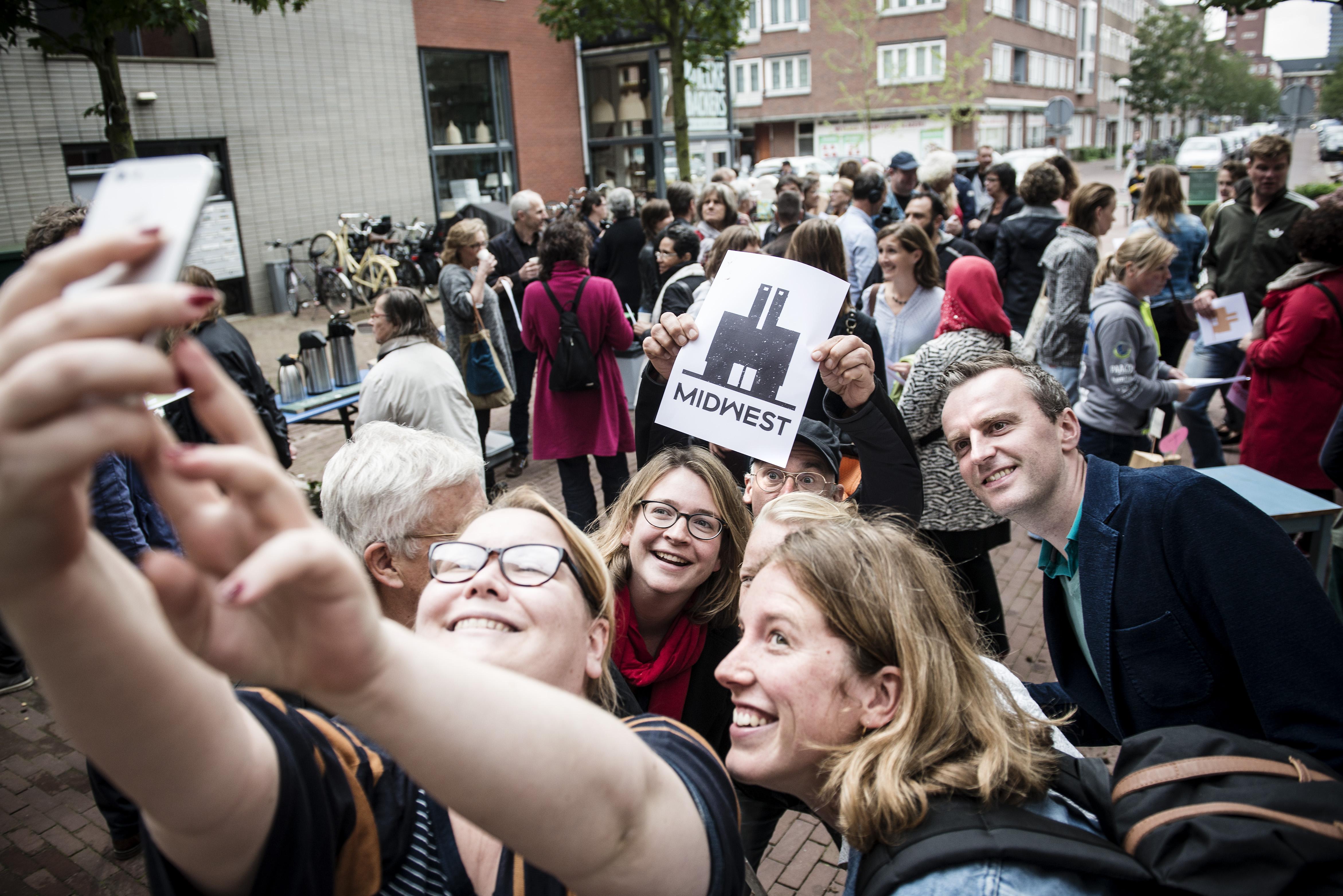 Nederland, Amsterdam, 20-09-2015  Enkele honderdden mensen verzamelen zich zondag om 15:00u voor de deur van MidWest om te 'staan voor MidWest'. De buurtonderneming in een oud schoolgebouw waar allerlerlei dingen voor de buurt worden georganiseerd en zzp-ers een werkplek huren wordt met sluiting bedreigd. De Gemeente wil niet meewerken aan het instandhouden van de plek. Sympatisanten maken een selfie op het plein voor het gebouw. foto: Bram Budel